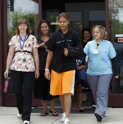 Amber Gray, a forward at the University of Tennessee basketball team, leaves the Drake Center in Hartwell, Ohio, with supporters, from left, physical therapist Kristy Black, mother Tonya Carter, and occupational therapist Diana Lee, on Tuesday.  Gray, 19, underwent elective surgery on July 2 to repair her rotator cuff. Post-surgery complications led to the discovery of an unrelated brain aneurysm that began to hemorrhage, causing a stroke.
