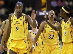 The Sparks' Lisa Leslie, left, gets a high-five from her teammates. She now has 6,010 career points.
