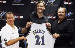 Newest Wizard Fabricio Oberto shows off his jersey with team president Ernie Grunfeld, right, and head coach Flip Saunders at Wednesday's news conference.