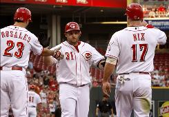 The Reds' Jonny Gomes, center, is congratulated by Adam Rosales, left, and Laynce Nix after Gomes hit a two-run homer in the second inning against the Nationals. The homer was one of three hit by Gomes on Thursday night.