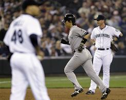 Mariners pitcher Ian Snell, left, and third baseman Jack Hannahan watch as the Yankees' Hideki Matsui rounds the bases after hitting a two-run homer in the third inning Thursday night.