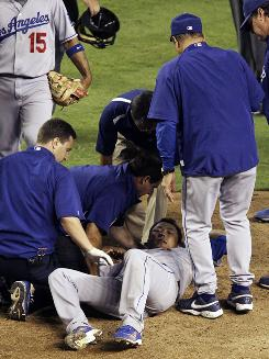 Los Angeles Dodgers pitcher Hiroki Kuroda of Japan lies on the ground as he is worked on by Dodgers medical staff after being hit in the head by a line drive by Arizona Diamondbacks' Rusty Ryal in the sixth inning of the Dodgers' 4-3 loss to the Diamondbacks in Phoenix.