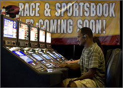 Kevin Duncan, 48, of Philadelphia, plays the slot machines near a sportsbook advertisement at Dover Downs racetrack in Dover, Del.