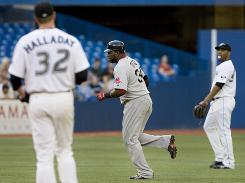 Blue Jays pitcher Roy Halladay, left, and teammate Edwin Encarnacion, right, watch as Red Sox DH David Ortiz rounds the bases following a solo home run in the second inning.