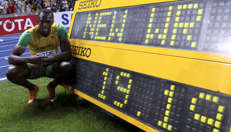 Jamaican Usain Bolt poses with the standard showing his world record time of 19.19 seconds in the 200 meters at the world championships in Berlin.