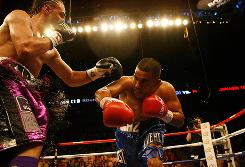 Paulie Malignaggi, left, and Juan Diaz battle in the second round Saturday at the Toyota Center in Houston.