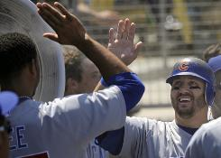 The Cubs' Jake Fox, right, is congratulated by teammates after hitting a solo homer in the second inning Sunday.