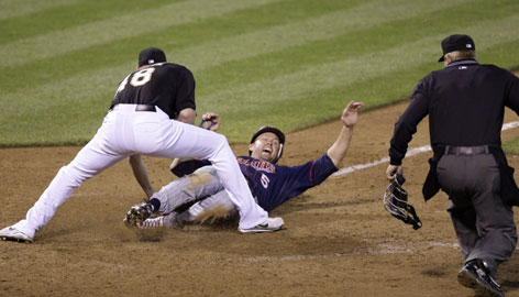 The Twins' Michael Cuddyer is called out to end the A's 14-13 win July 20. Umpire Mike Muchlinski's call couldn't be overruled because replays aren't used for safe or out calls on the bases.