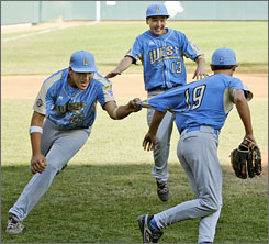 Chula Vista, Calif., first baseman Luke Ramirez, left, celebrates with pitcher Kiko Garcia, right, and third baseman Seth Godfrey (13) after the last out in Chula Vista's 6-3 win over Taoyuan, Taiwan, in the Little League World Series championship baseball game in South Williamsport, Pa.