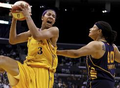 The Los Angeles Sparks' Candace Parker, left, grabs a rebound away from the Connecticut Sun's Tamika Whitmore during the first half of the Sparks' 91-81 victory on Sunday.