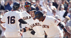 Edgar Renteria, No. 16, receives a hero's welcome from Giants mates Fred Lewis (second from left), Aaron Rowand and Juan Uribe (right) after hitting his grand slam helped beat the Rockies on Sunday.