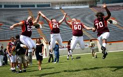 Virginia Tech players, from left, Blake DeChristopher, Cody Grimm, Beau Warren and Sergio Render leap Aug. 8 during media day.