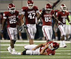 Oklahoma players look on as quarterback Sam Bradford holds his injured shoulder.