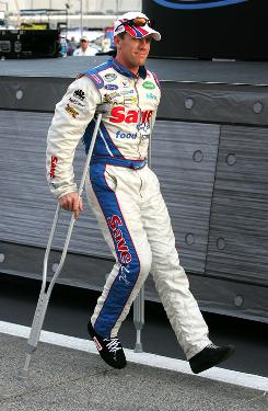 Sprint Cup driver Carl Edwards uses crutches at Saturday night's Nationwide Series Degree V12 300 race. He fractured his right foot playing Frisbee earlier in the week, but will be behind the wheel Sunday.