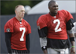 Jeff Garcia, left, was signed by the Raiders in the offseason to push and mentor JaMarcus Russell, right. Instead, Garcia was cut by Oakland on Saturday.