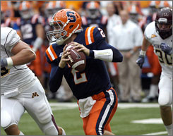 Syracuse quarterback and former Duke basketball player Greg Paulus rolls out with the ball in the second quarter of the Orange's loss to Minnesota on Saturday.