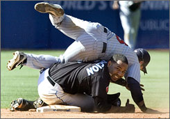 Toronto baserunner Edwin Encarnacion upends Minnesota infielder Nick Punto, but slides in too late at second base for an out.