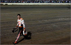 Joey Logano walks back to the pits after crashing during Wednesday night's charity dirt-track race at Eldora Speedway in Ohio.
