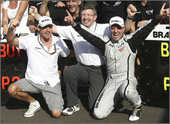 Italian GP winner Rubens Barrichello, right, celebrates with team boss Ross Brawn and runner-up Jenson Button after leading a team sweep at Monza.