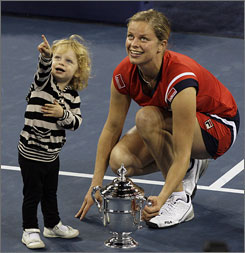 Kim Clijsters and her daughter Jada pose with the championship trophy after she defeated Caroline Wozniacki in the women's final. Clijsters also won the U.S. Open in 2005, the last time she played in the tournament.