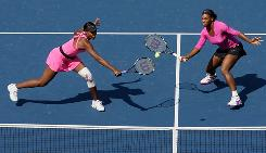 Venus, left, and Serena Williams reach for a shot in their straight-sets victory Monday against Liezel Huber and Cara Black in the women's doubles final at the U.S. Open.