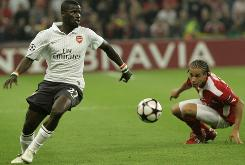 Arsenal player Emmanuel Eboue, left, and Standard Liege player Axel Witsel in action during their Champions League match Wednesday in Liege, Belgium.
