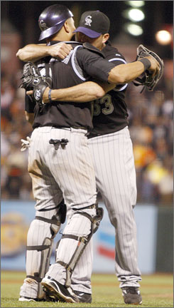 Rox reliever Rafael Betancourt embraces catcher Yorvit Torrealba after Colorado escaped a Giants rally in the ninth for a 4-3 victory on Wednesday.