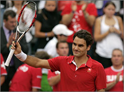 Roger Federer waves to Swiss fans after helping his country to a 2-0 lead against Italy in Davis Cup play.