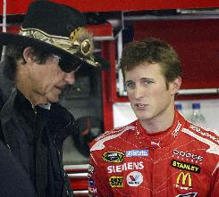Driver Kasey Kahne, right, talks with team owner Richard Petty in the garage area while preparing for Sunday's NASCAR Sprint Cup series Sylvania 300 at New Hampshire Motor Speedway.