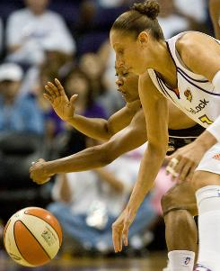 The Phoenix Mercury's Diana Taurasi, front, and the San Antonio Silver Stars' Vickie Johnson chase a loose ball during their WNBA Western Conference semifinal in Phoenix. Phoenix beat San Antonio 106-78 to even the series.