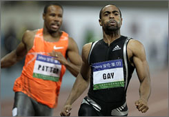 Tyson Gay pulls up after the finish of the men's 100 meters alongside follow American Darvis Patton.