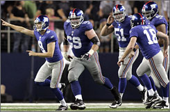Giants teammates chase kicker Lawrence Tynes after his 37-yard field goal as time expired beat the Cowboys 33-31.