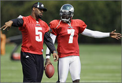 Michael Vick, right, consults with Donovan McNabb during Eagles workouts on Wednesday.