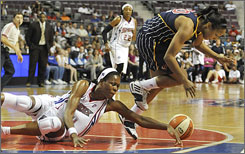 Detroit Shock's Taj McWilliams, left, dives for a loose ball against Indiana's Briann January in Game 1 of the Eastern Conference finals.