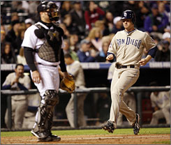 The Padres' Chase Headley, right, scores on a single by Nick Hundley as Rockies catcher Chris Iannetta looks on in the eighth inning of the Padres' 5-4 victory.