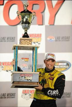 Johnny Sauter hoists the winner's trophy after winning the NASCAR Camping World Truck Series Las Vegas 350 on Saturday night.
