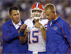 Tim Tebow is helped off the field by trainers after taking a hit from Kentucky's Taylor Wyndham in the Gators' 41-7 victory on Saturday. Tebow left the game and spent the night at a hospital in Lexington, but has been released and will return to Florida.
