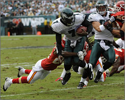 The Eagles' Michael Vick is tackled by the Chiefs' Brandon Flowers during Philadelphia's 34-7 victory on Sunday.