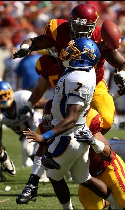 San Jose State Spartans quarterback Kyle Reed is hit by University of Southern California defensive end Nick Perry (No. 8) and defensive tackle Derek Simmons (No. 90) as he releases a pass on Sept. 5. It is unclear whether Perry will be able to play Saturday against No. 19 California.
