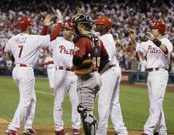 The Philadelphia Phillies' Pedro Feliz, left, celebrates with teammates Raul Ibanez, Ryan Howard and Jayson Werth as Houston Astros catcher J.R. Towles looks on. Feliz hit a grand slam in the fourth inning as Philadelphia won 7-4.