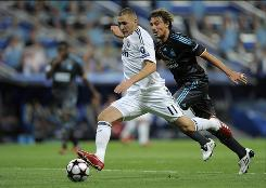 Real Madrid's Karim Benzema, left, duels for the ball with Olympique de Marseille Gabriel Heinze during their Group C Champions League match in Madrid, Wednesday. Real Madrid won 3-0.