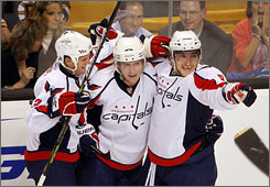 The Capitals' Alex Ovechkin, right, celebrates with teammates Tom Poti, left, and Nicklas Backstrom after scoring a second-period goal against the Bruins in Boston.