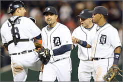 The Detroit Tigers are wearing smiles as they move just one game from clinching the American League's Central crown. Catcher Gerald Laird, left, joins second baseman Placido Polanco, third baseman Brandon Inge and shortstop Ramon Santiago after the Tigers stopped the Minnesota Twins on Wednesday.