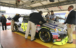 NASCAR officials inspect Jimmie Johnson's car Friday before qualifying at the track in Kansas City.