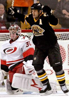 Boston Bruins' Marco Sturm celebrates a goal by teammate Michael Ryder as Carolina Hurricanes goalie Cam Ward looks on during their game at TD Garden in Boston.
