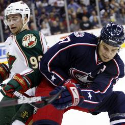 The Columbus Blue Jackets' Rostislav Klesla, right, of Russia, clears the puck away from the Minnesota Wild's Pierre-Marc Bouchard, left, during their game in Columbus, Ohio. The Blue Jackets won 2-1.