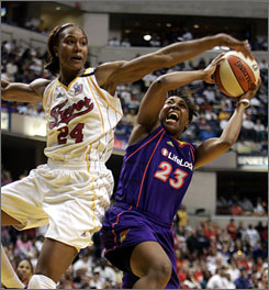 Indiana Fever forward Tamika Catchings, left, tries to block the shot of Phoenix Suns guard Cappie Pondexter.