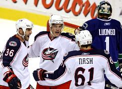 The Columbus Blue Jackets' Mathieu Roy, left, Antoine Vermette, and Rick Nash celebrate Vermette's goal on Vancouver Canucks goalie Roberto Luongo. The Blue Jackets beat the Canucks 5-3.