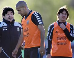 Argentina's coach Diego Maradona, left, talks to player Juan Sebastian Veron, center, as teammate Lionel Messi looks on during training Tuesday. Maradona said Tuesday that he may resign after the team's two World Cup qualifying matches in the coming week.