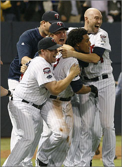Twins players mob Alexi Casilla, center, after he drove in the winning run in the bottom of the 12th inning against the Tigers.
